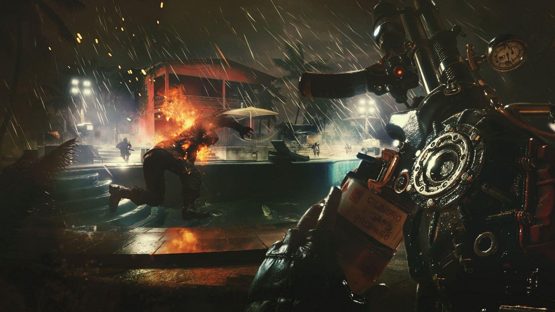 Imagem em primeira pessoa do jogo Far Cry 6 em um resort em uma área externa com chuva. Na parte direita da imagem o jogador segura um lança-chamas improvisado e na esquerda uma pessoa ferida pelas chamas