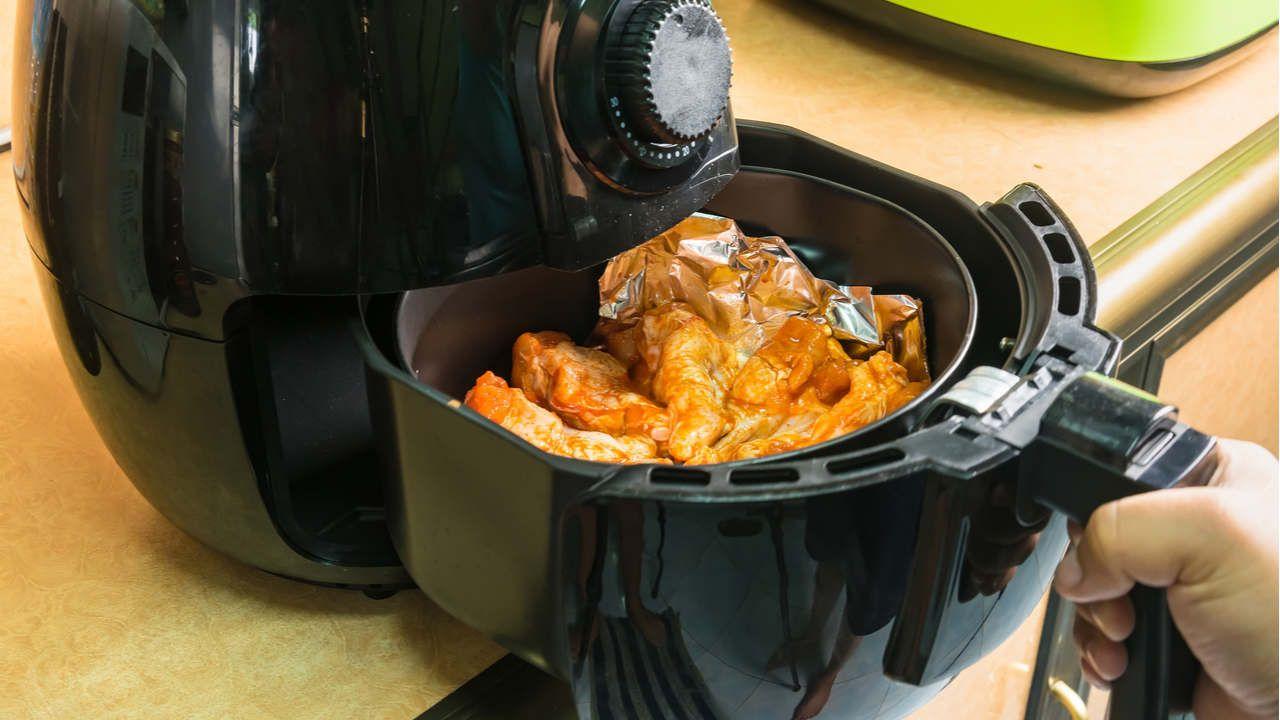 Mão segurando alça de air fryer aberta, com frangos fritos dentro