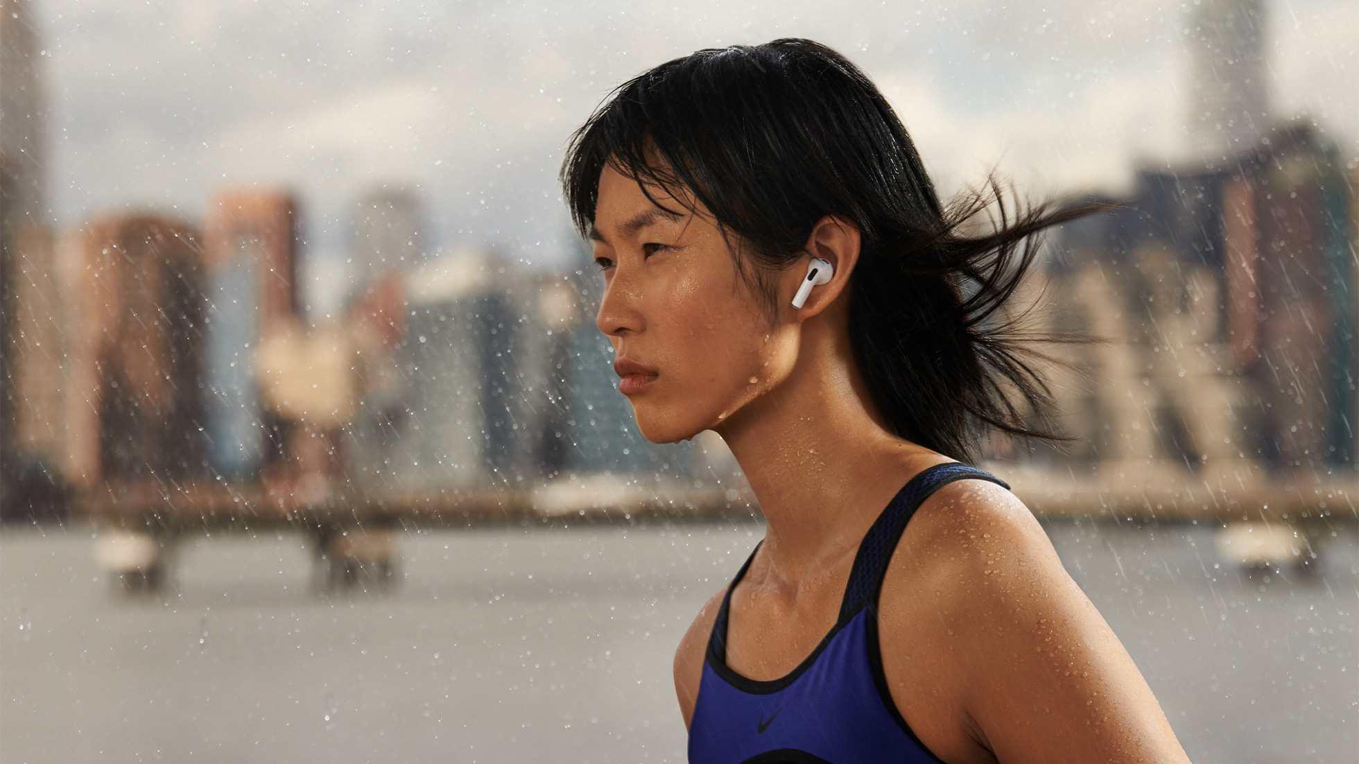 Mulher oriental corre usando o Airpods 3 com cidade ao fundo