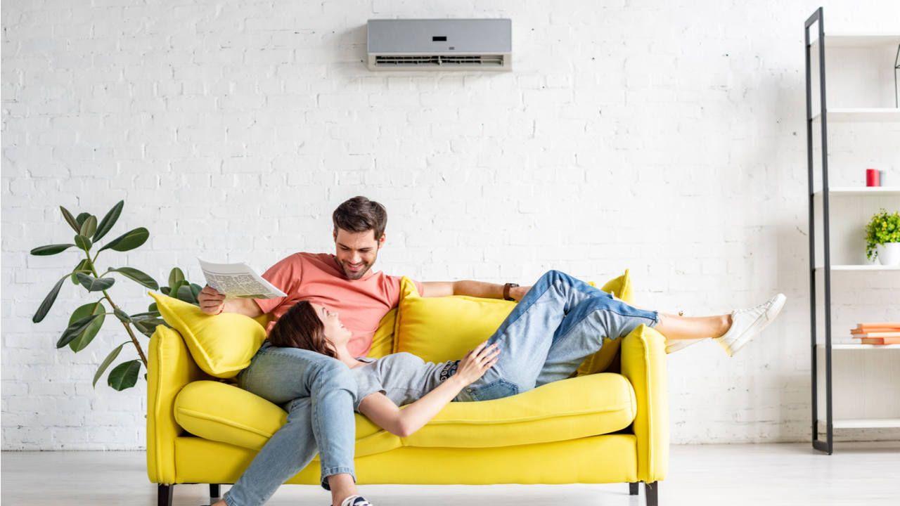 Casal à vontade em sofá amarelo em sala de estar com ar-condicionado split na parede