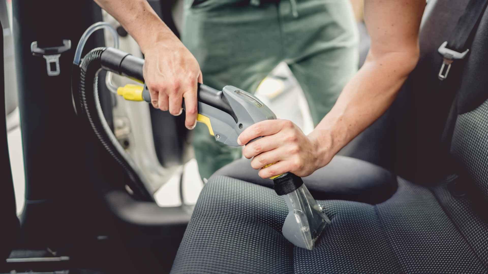 Homem aspirando banco de carro com aspirador de pó