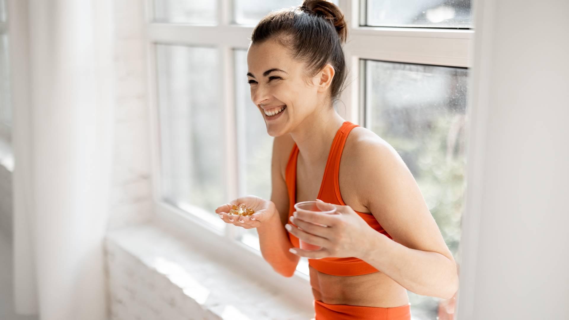 Mulher segurando copo de água e cápsulas