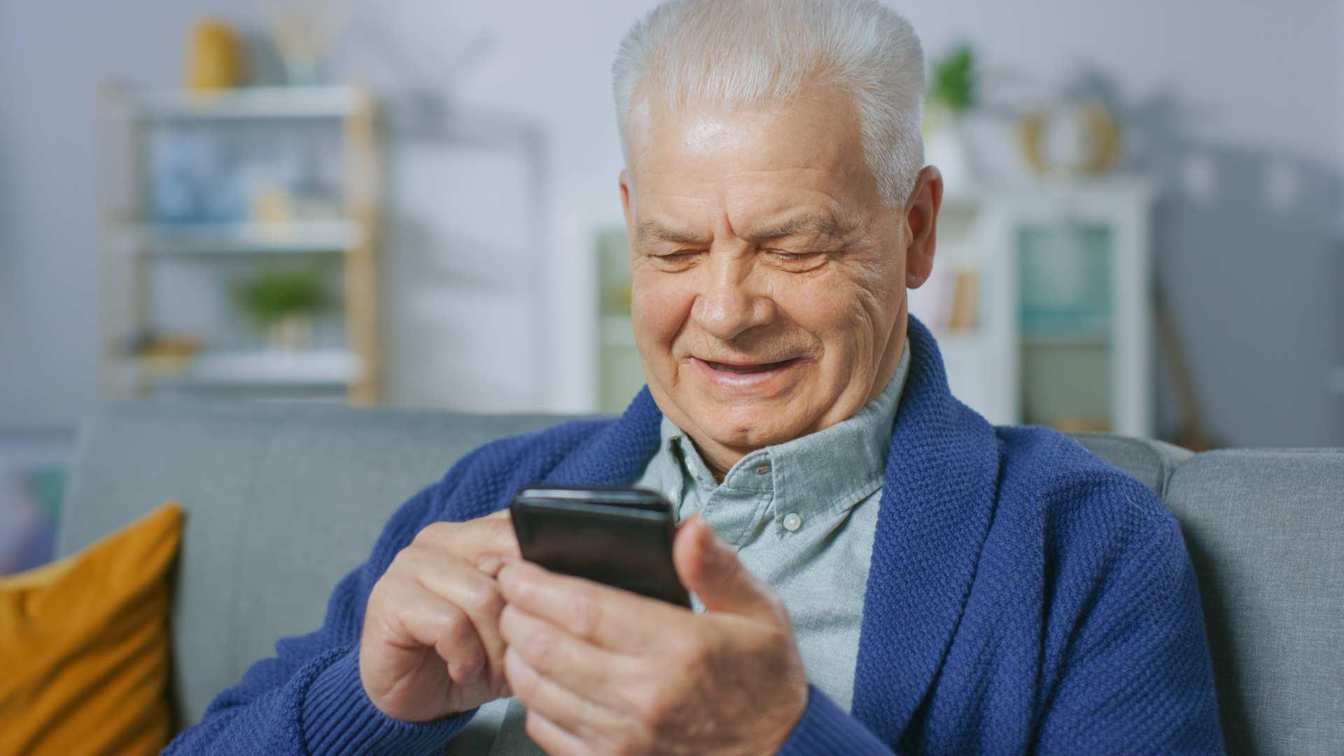 Senhor de casaco azul sentado em sofa usando celular para idoso