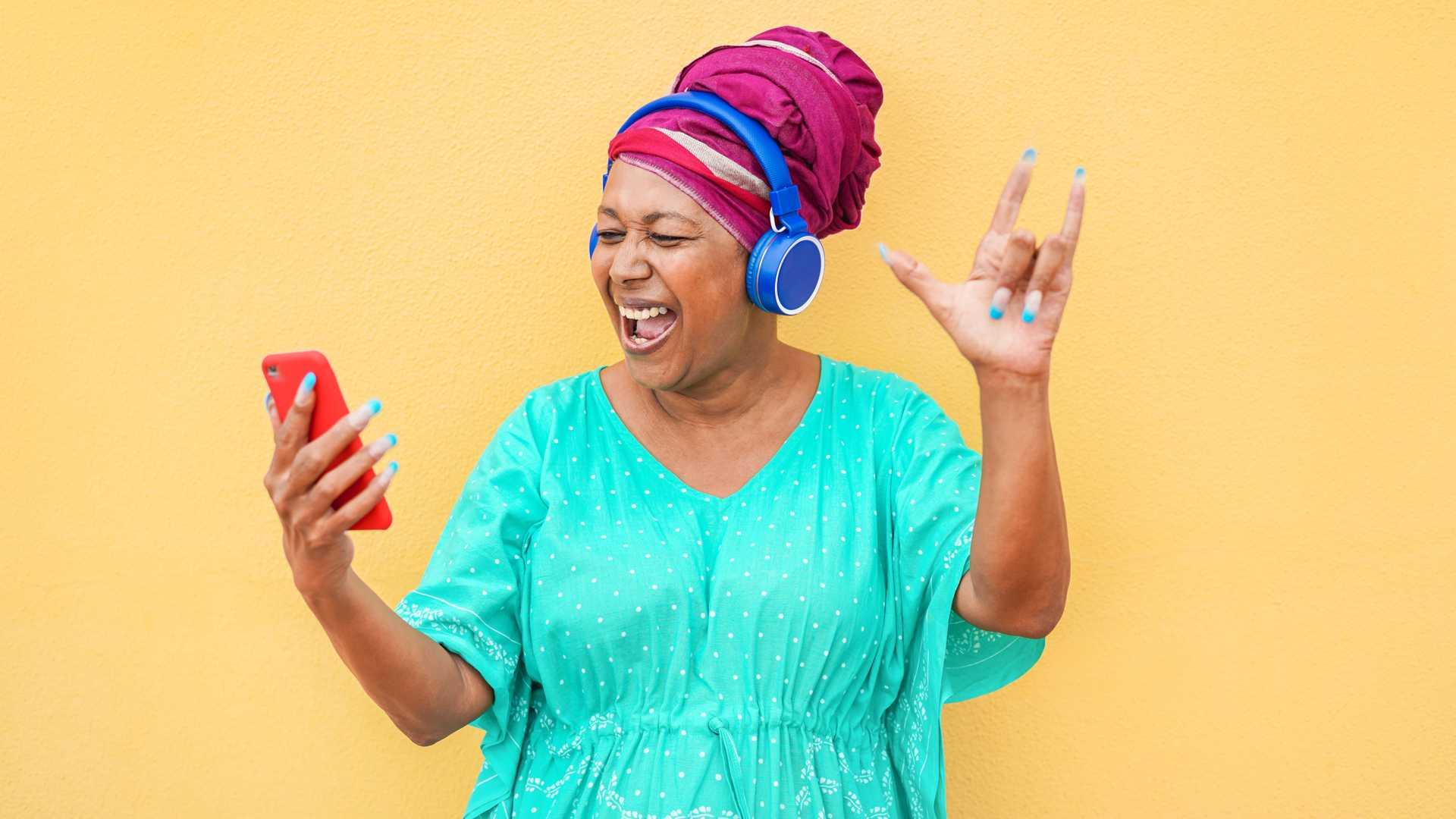 Mulher de camisa azul escuta música em seu celular para idoso
