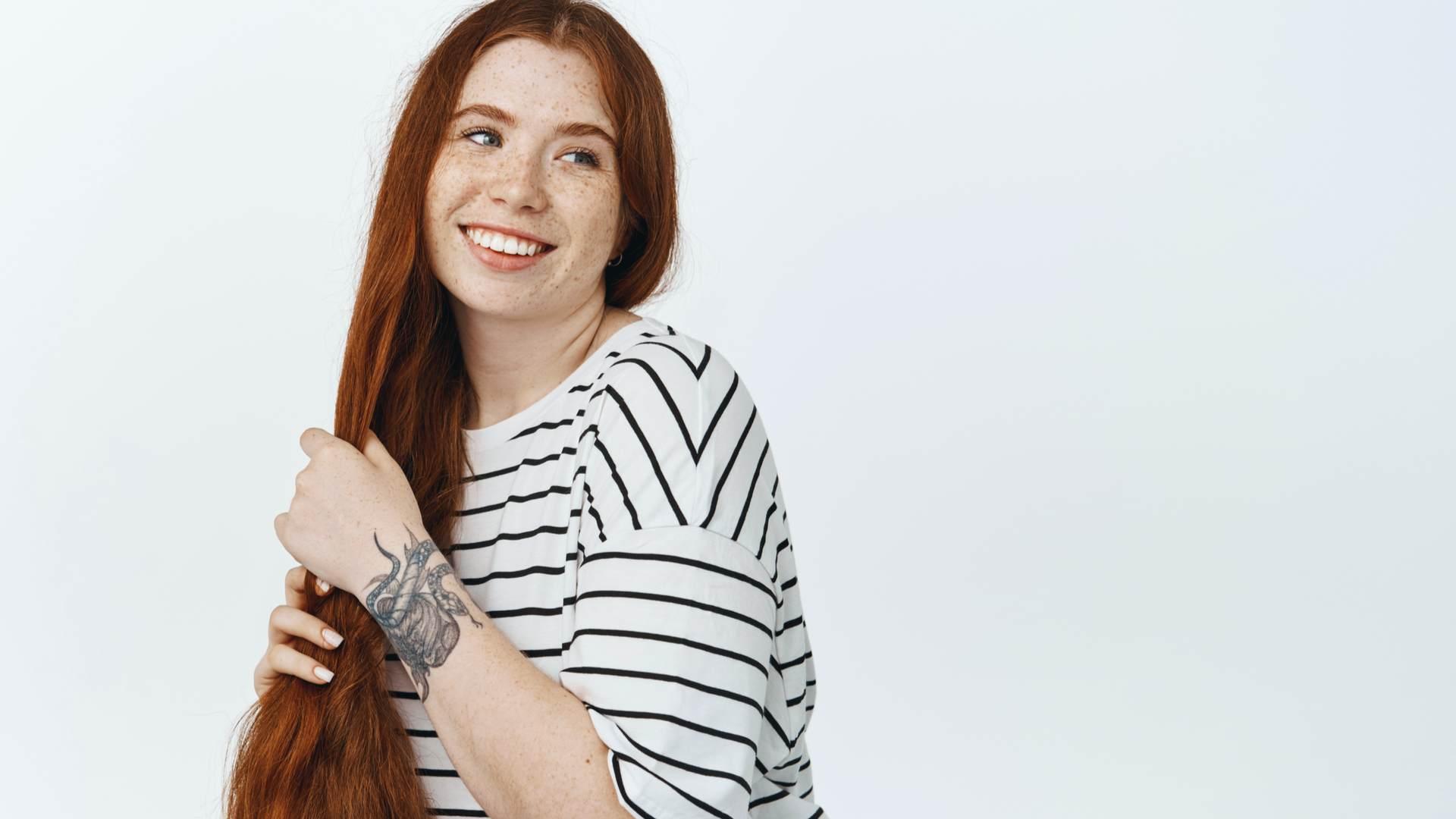 Mulher ruiva de cabelos longos passando a mão nos fios