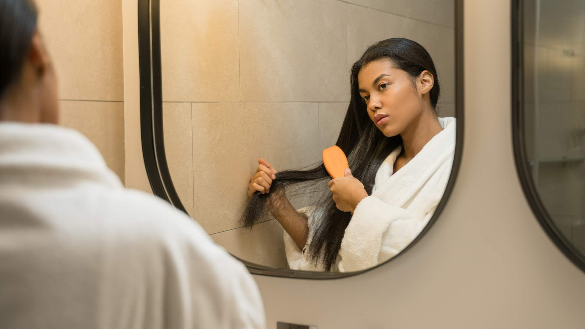 Mulher morena de cabelos lisos e pretos penteando os fios no espelho