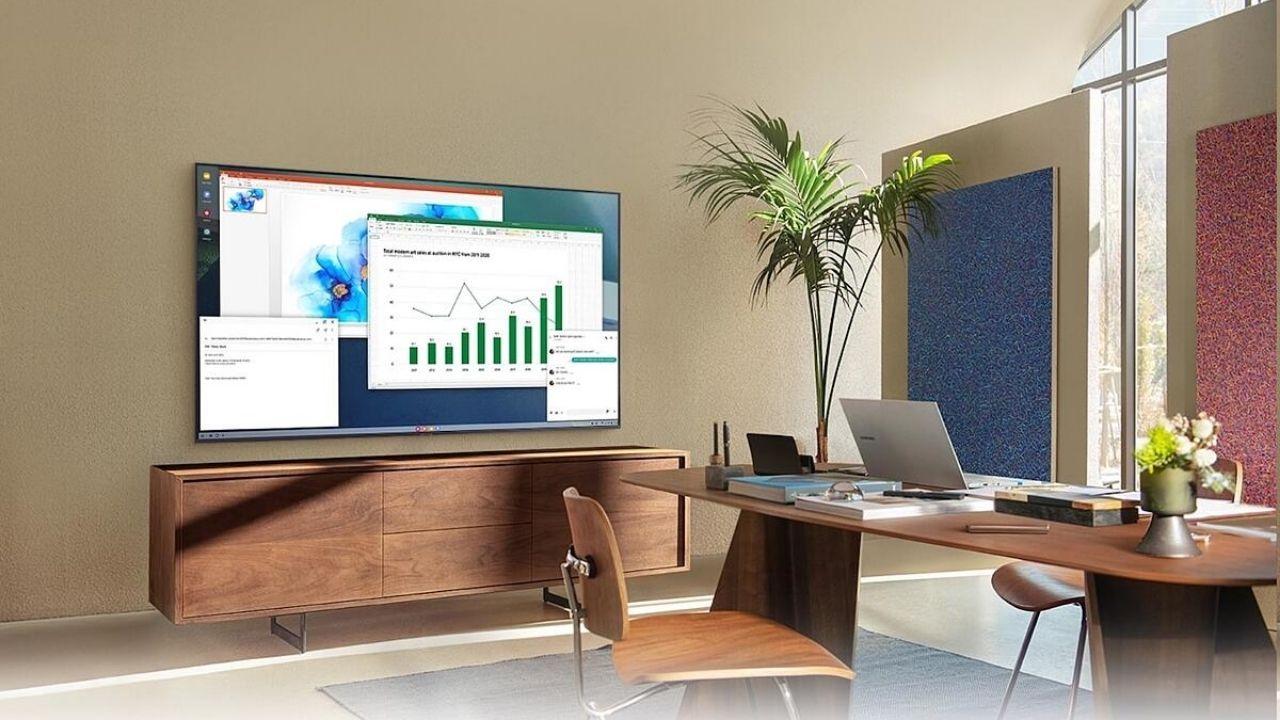 Escritório com notebook Samsung sobre escrivaninha e smart TV na parede exibindo planilhas e gráficos