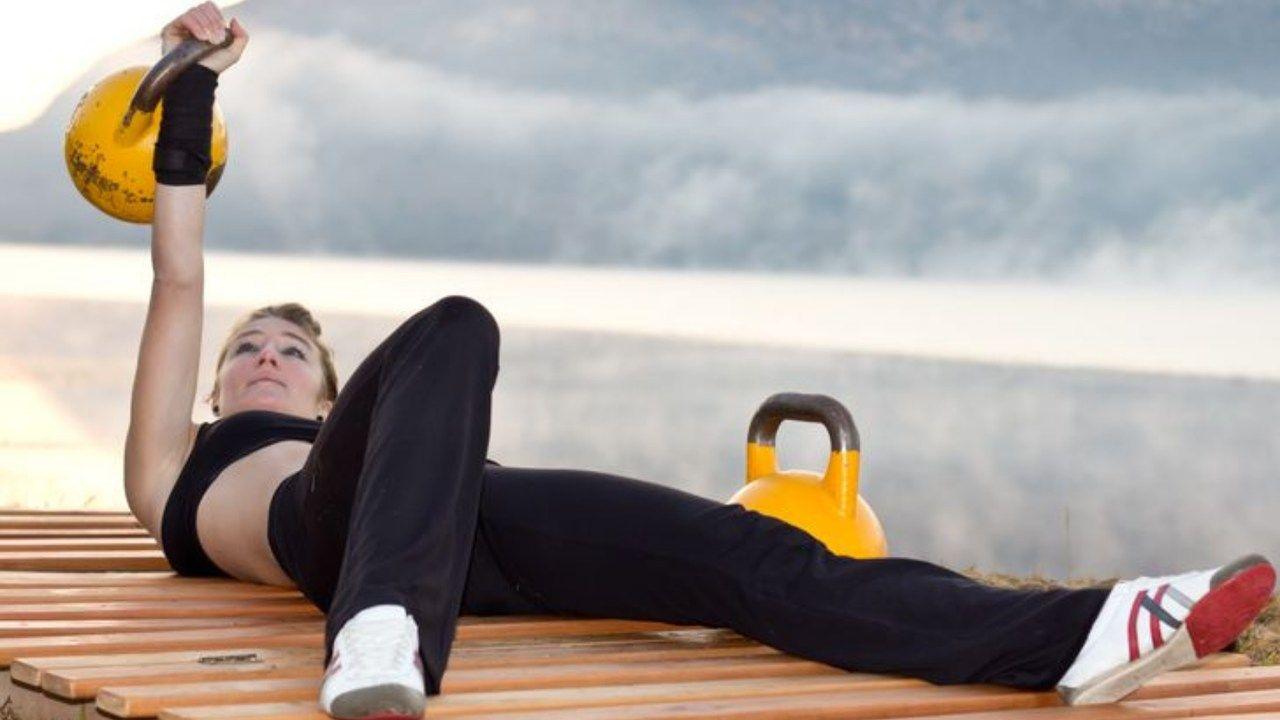 Mulher fazendo prensa no chão com kettlebell perto de um lago
