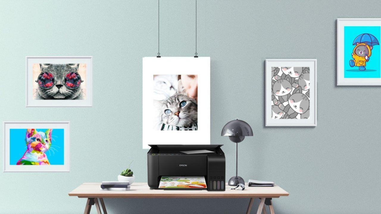 Impressora Epson Ecotank preta em cima de mesa de madeira com  parede azul clara ao fundo