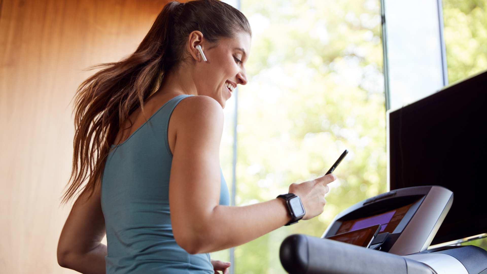 Mulher correndo na esteira em casa e mexendo no celular