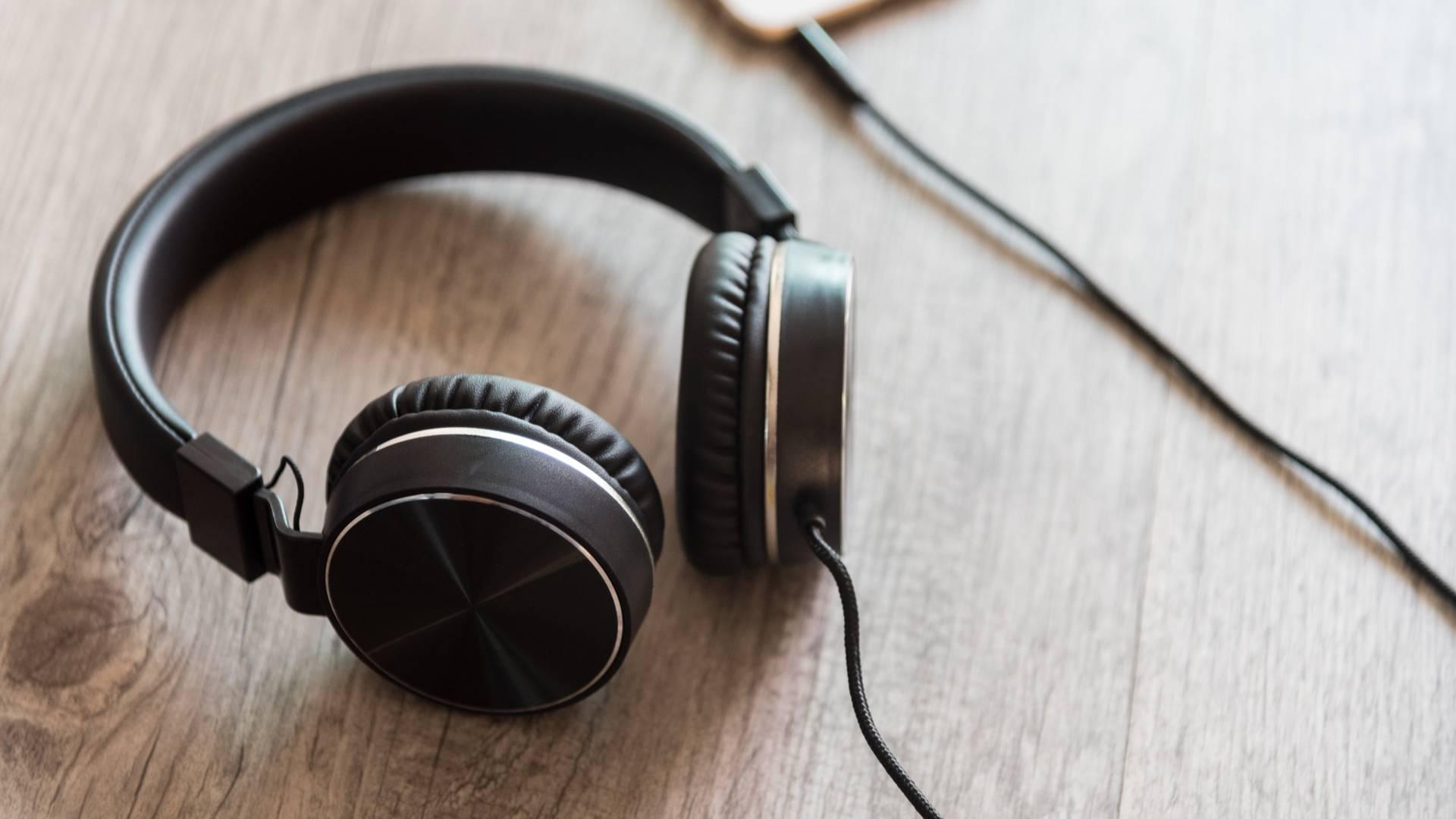 Fone de ouvido plugado em um celular em cima da mesa