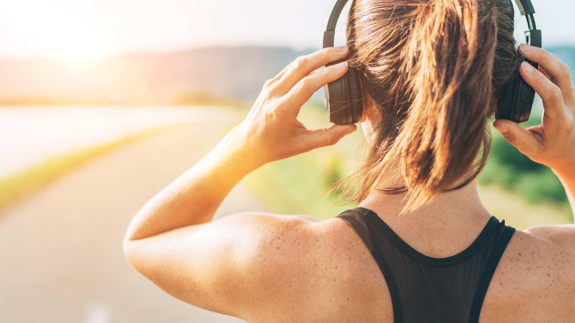 Mulher prestes a caminhar e usando um fone de ouvido sem fio
