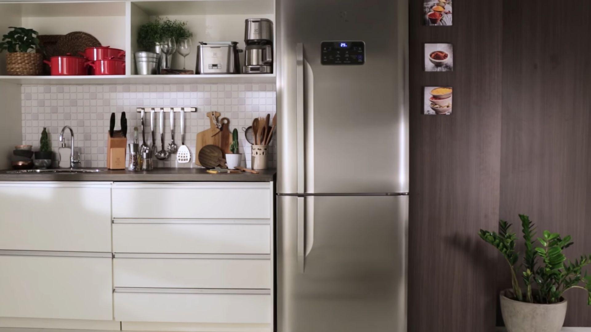 Geladeira inverse inox ao centro de uma cozinha, tendo armários brancos com detalhes em madeira à esquerda cheios de utensílios sobre eles