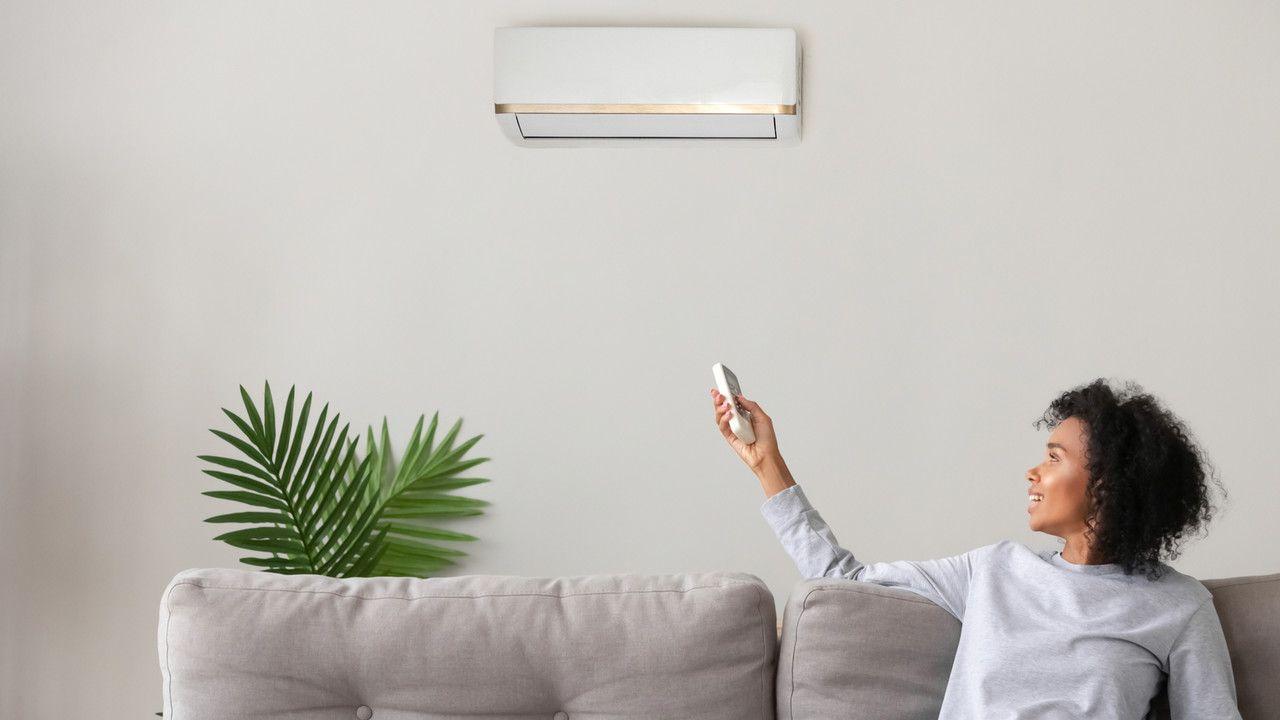 Mulher de cabelo cacheado apontando controle remoto para um ar-condicionado split branco instalado em parede