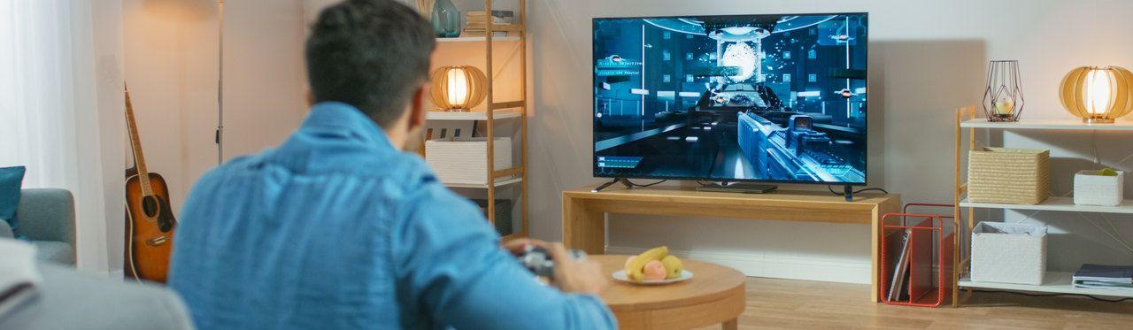 Homem sentado em um sofá enquanto joga em um videogame