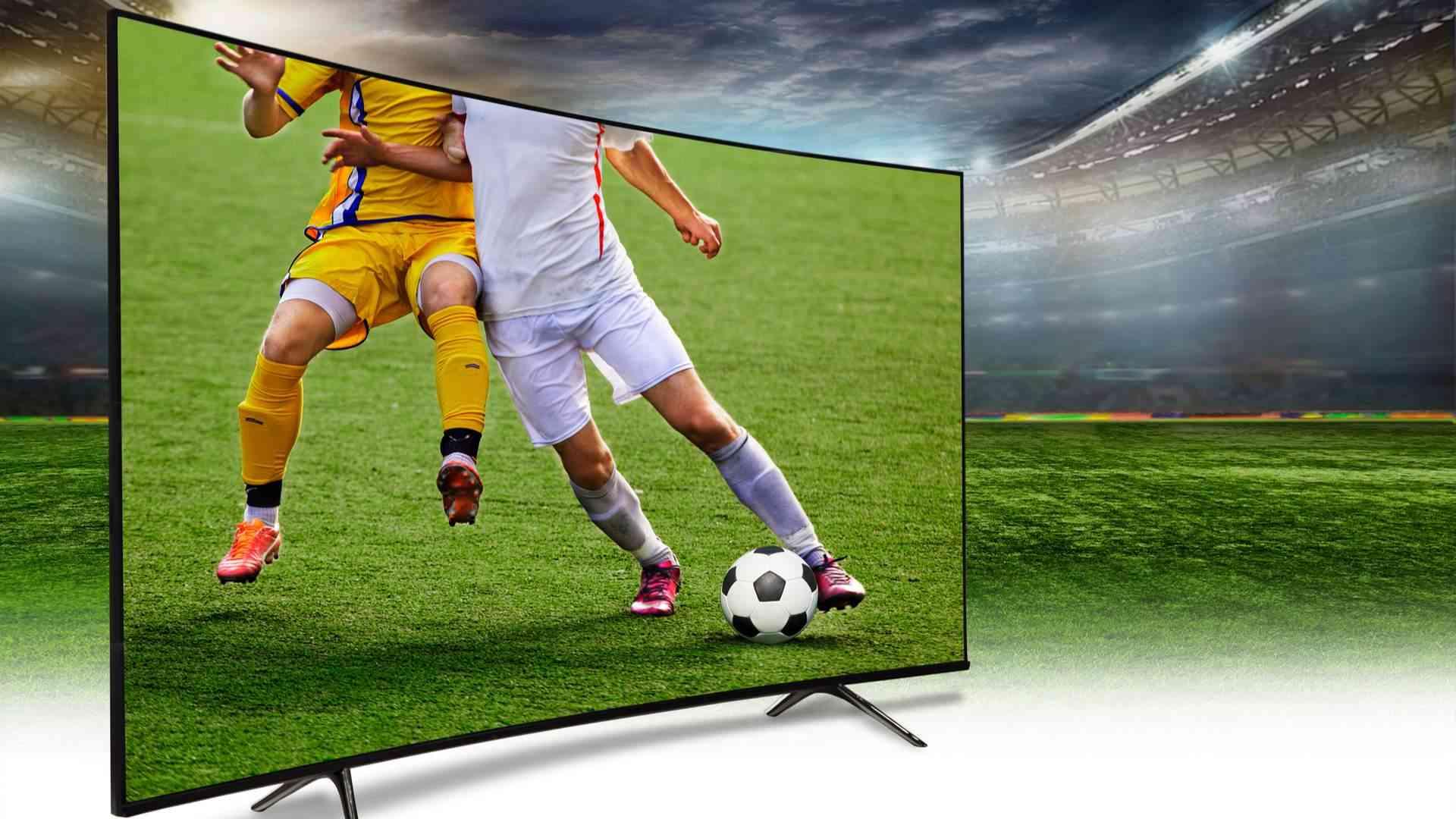 Monitor exibindo partida de futebol sobre ilustração futebolística ao fundo