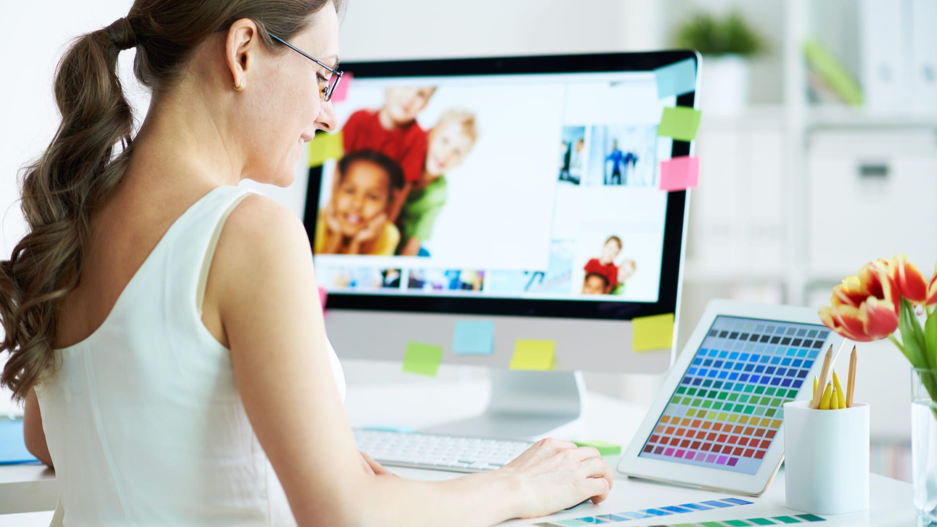 Mulher branca em escritório com monitor em frente, mas olhando para um tablet exibindo paleta de cores ao lado