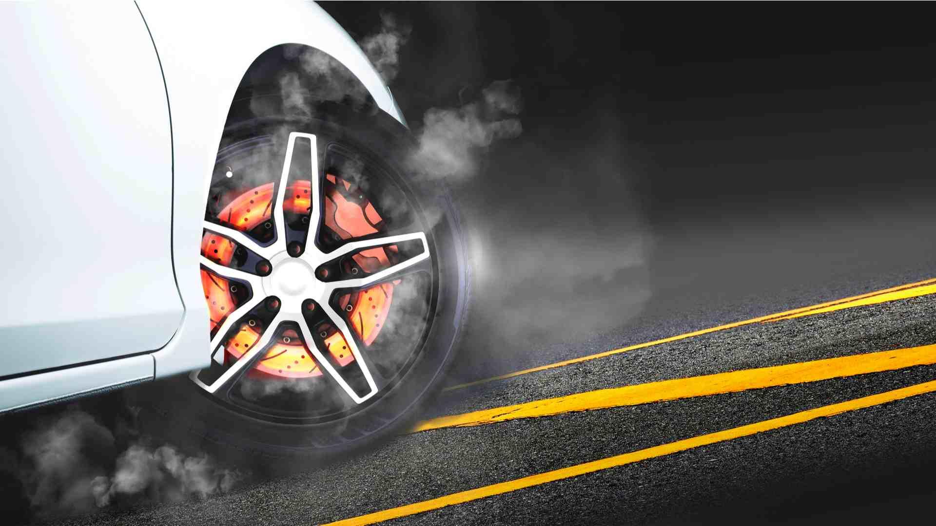 Disco e pastilha de freio muito quentes de carro branco em asfalto
