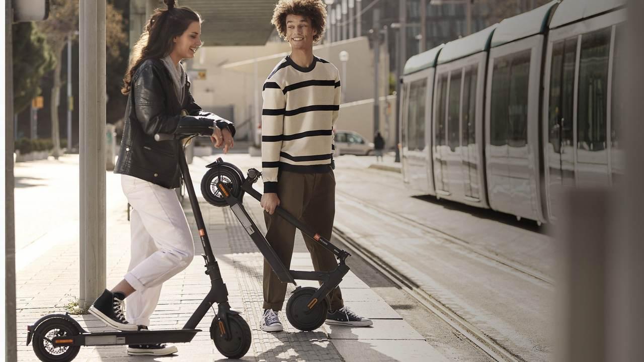 Dois jovens lado a lado, rindo enquanto esperam na calçada. A mulher, apoia o pé no patinete elétrico Xiaomi montado. Já o rapaz, segura o patinete Xiaomi Essential dobrado na mão esquerda