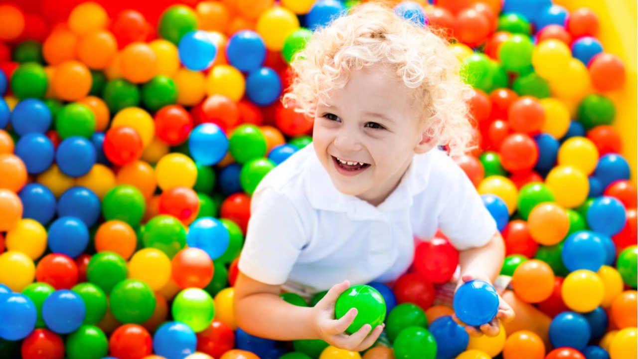Criança pequena branca e loira em piscina de bolinhas coloridas