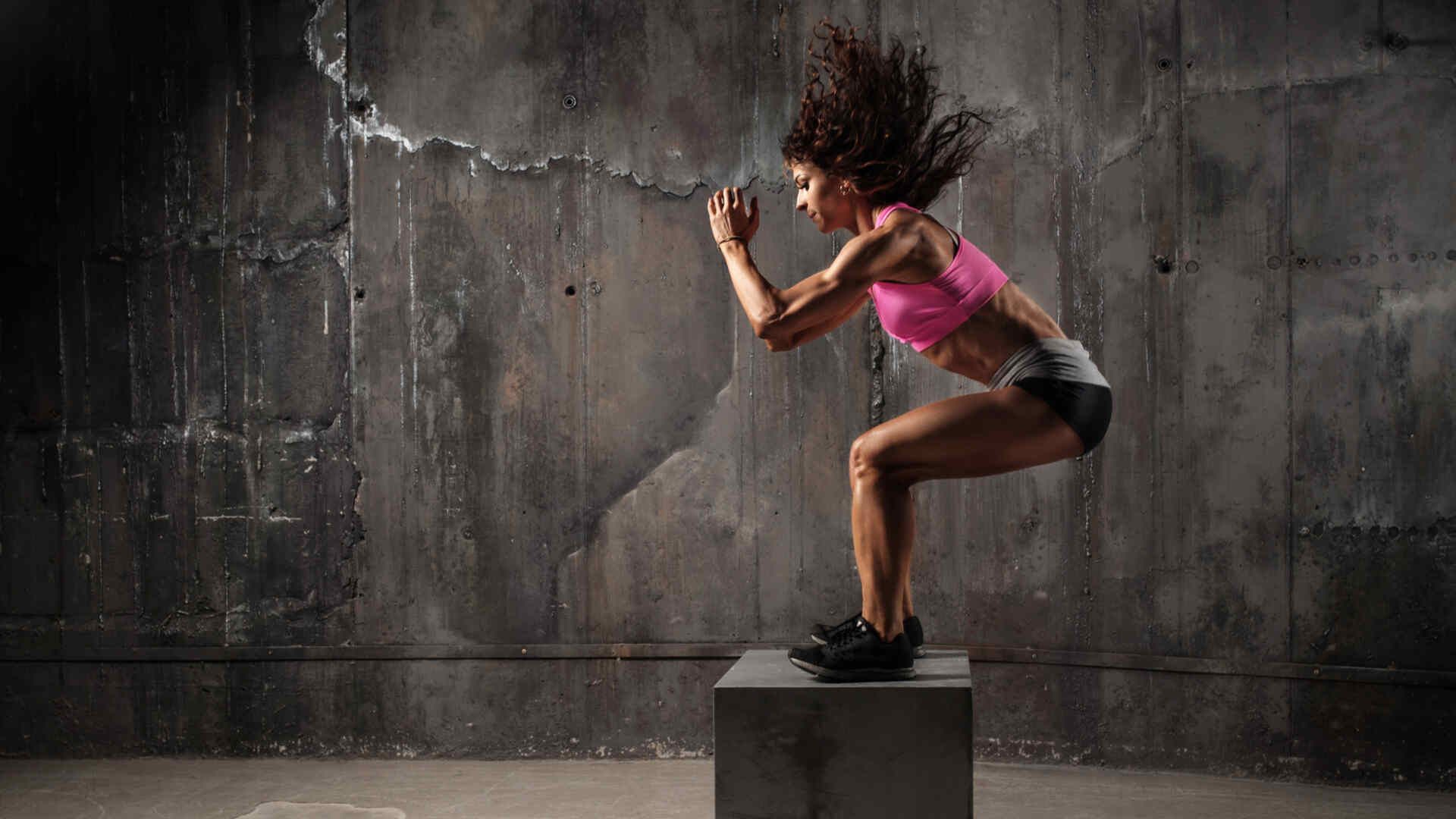 Mulher negra pulando em caixote na frente de fundo cinza