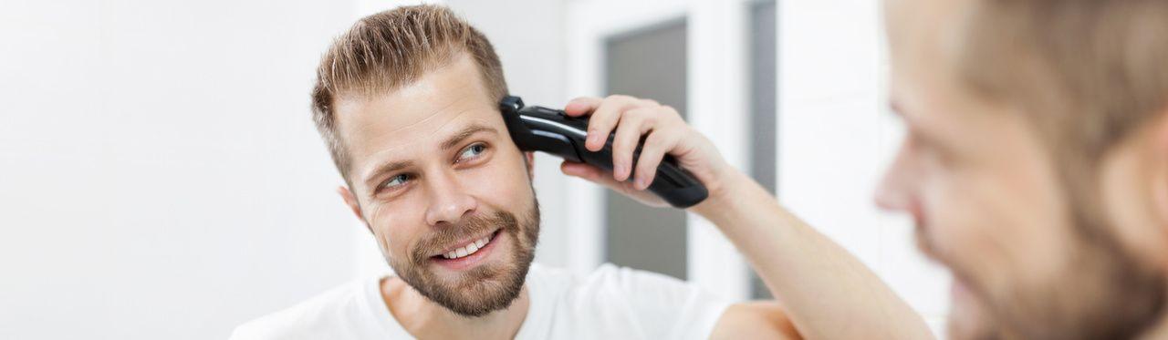 Homem branco e barbudo cortando o próprio cabelo com uma máquina de cortar cabelo sem fio