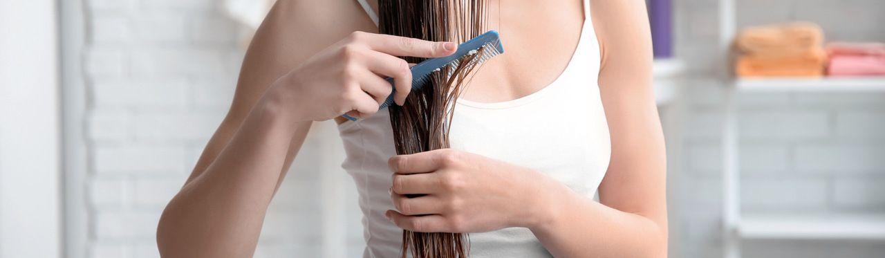 Mulher caucasiana jovem penteando o cabelo depois de aplicar queratina nos fios