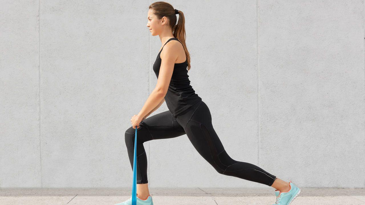 Mulher jovem vestindo roupas de ginástica pretas, elástico azul apoiado embaixo do tênis e sendo puxado pelas mãos, acima do joelho semiflexionado, em movimento de passada frontal