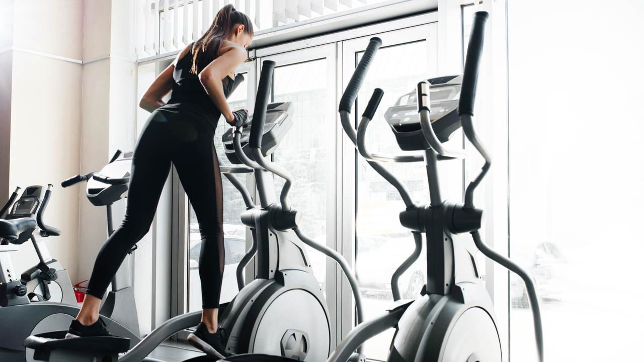 Mulher jovem em academia, fazendo exercício em elíptico com inclinação para a frente, utilizando roupas de ginástica pretas