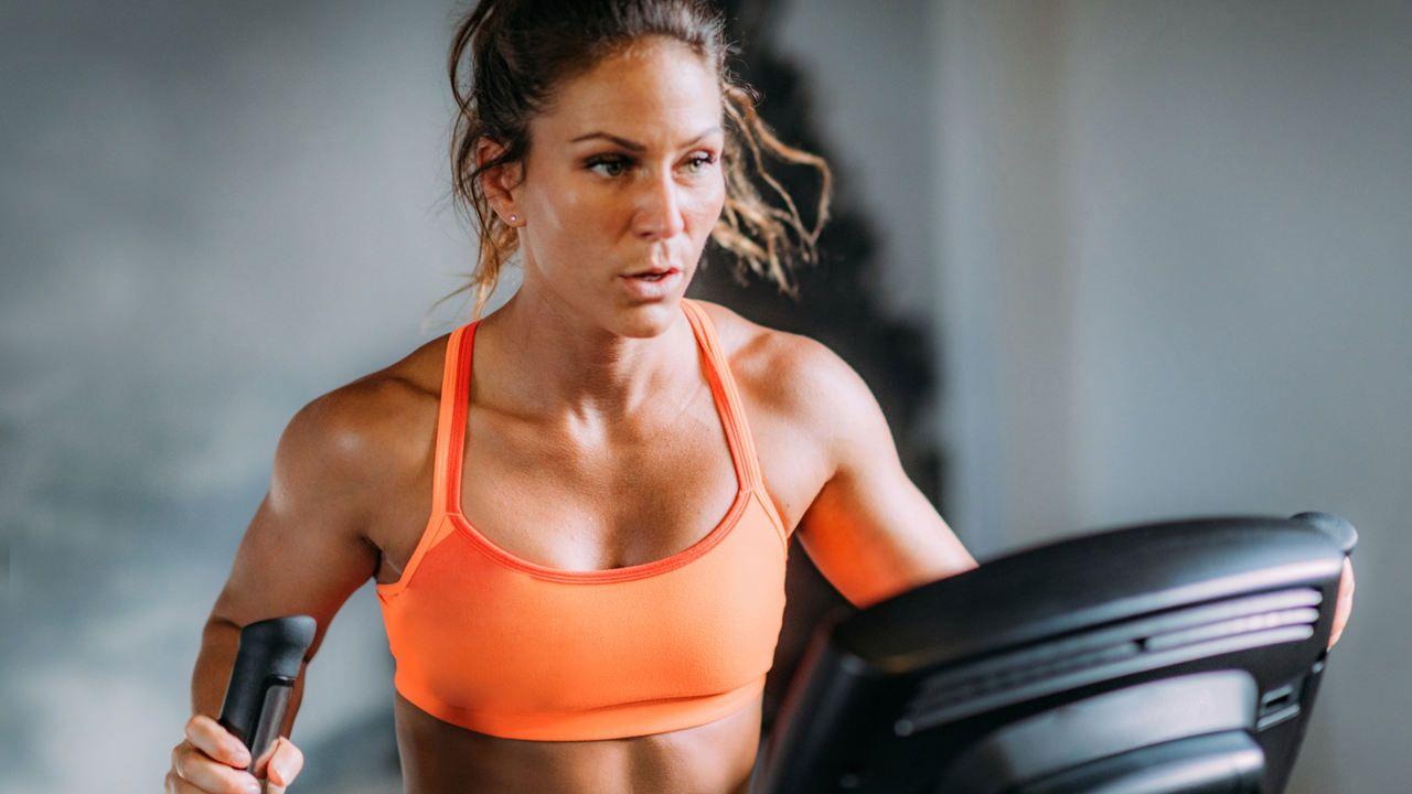 Mulher jovem vista da cintura para cima, fazendo esforço físico em aparelho elíptico e usando top de ginástica laranja