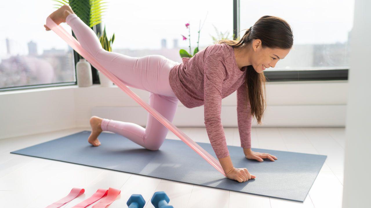 Mulher asiática utilizando roupas de exercício cor-de-rosa, fazendo exercício para glúteos em casa com a ajuda de elástico de treino, apoiada sobre joelhos e mãos em tapete de yoga