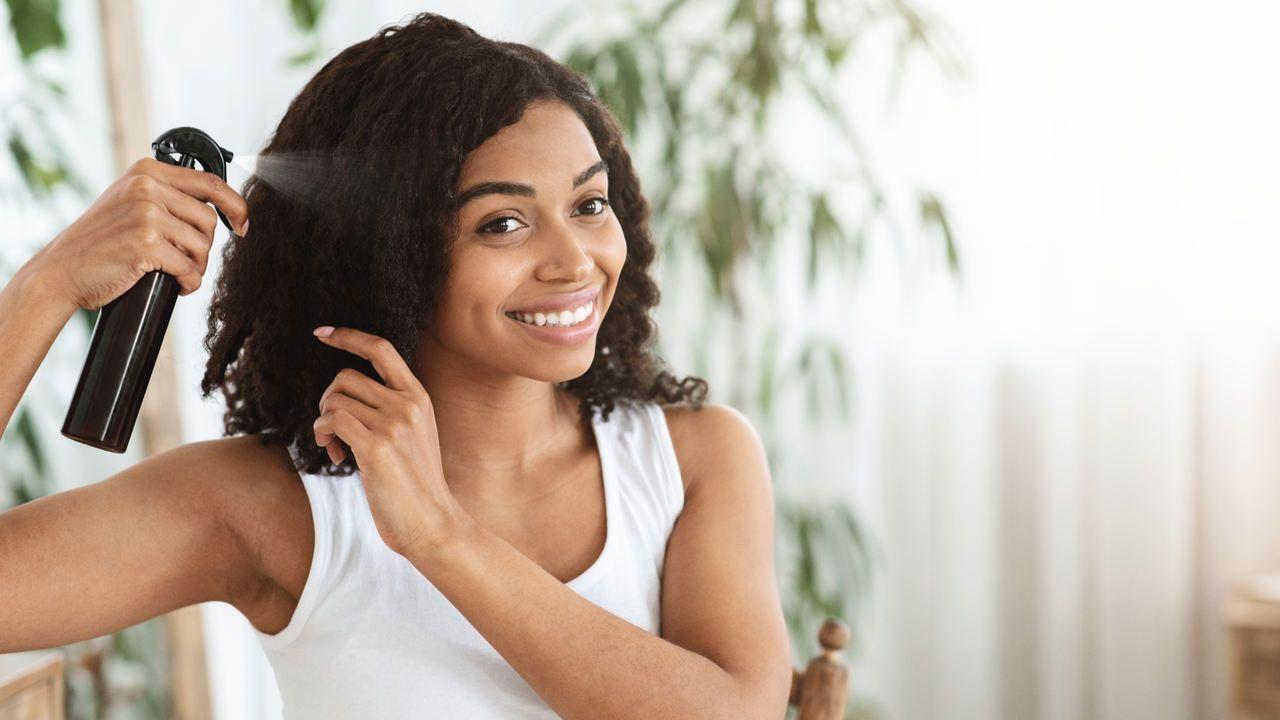 Mulher negra sorridente aplicando queratina líquida nos seus cabelos cacheados em casa
