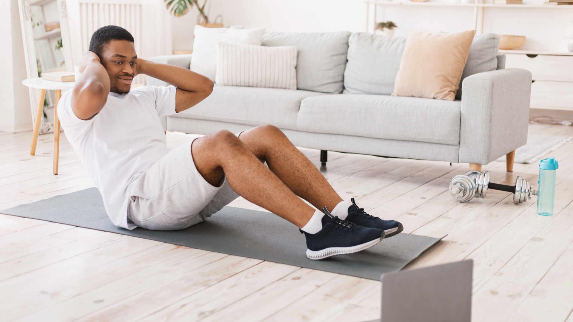 Homem negro fazendo abdominal em sua sala de estar