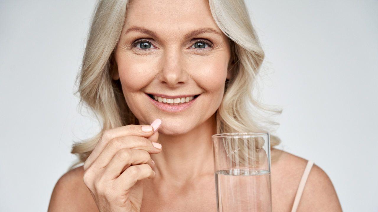 mulher branca de meia idade segura uma cápsula com uma mão e um copo de água na outra