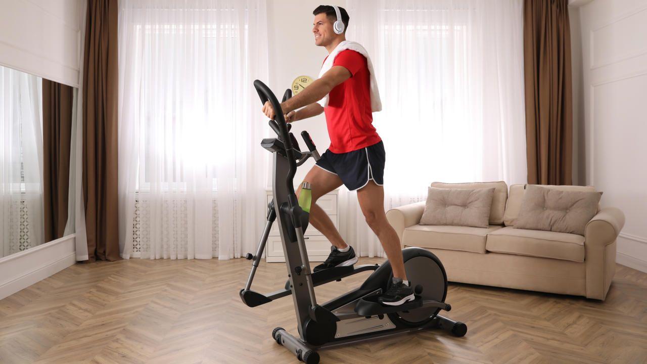 Homem jovem fazendo exercício em casa com transport elíptico, vestindo camiseta laranja e shorts pretos, fones nos ouvidos e toalha sobre os ombros