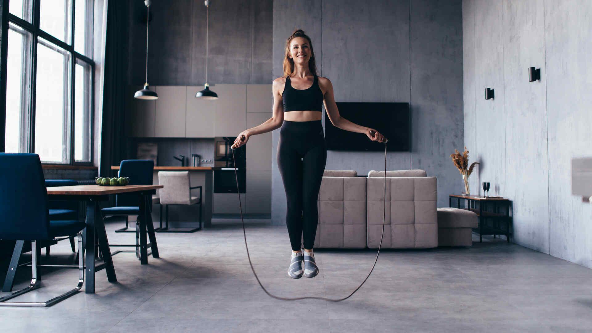 Mulher caucasiana pulando corda em sala de estar