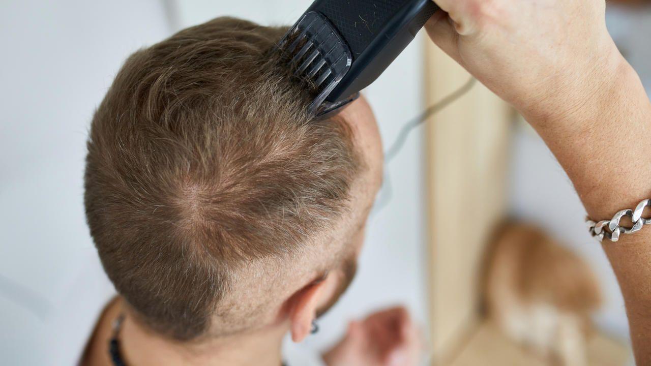 Homem branco raspando o próprio cabelo com uma máquina de cortar cabelo e barba