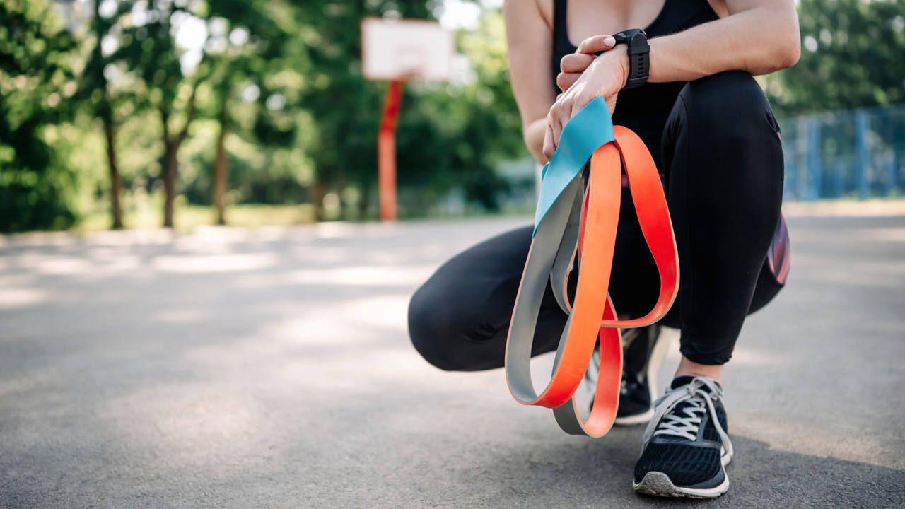 Moça jovem com roupas de ginástica agachada em quadra de basquete, segurando nas mãos um kit com elásticos para treino nas cores cinza e laranja