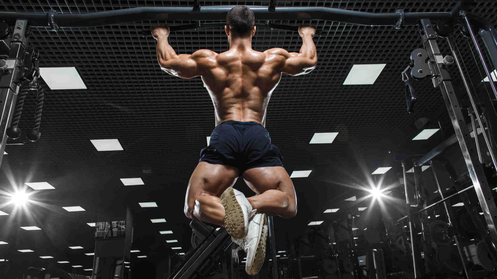 Homem caucasiano fazendo exercício de barra sem camisa em academia