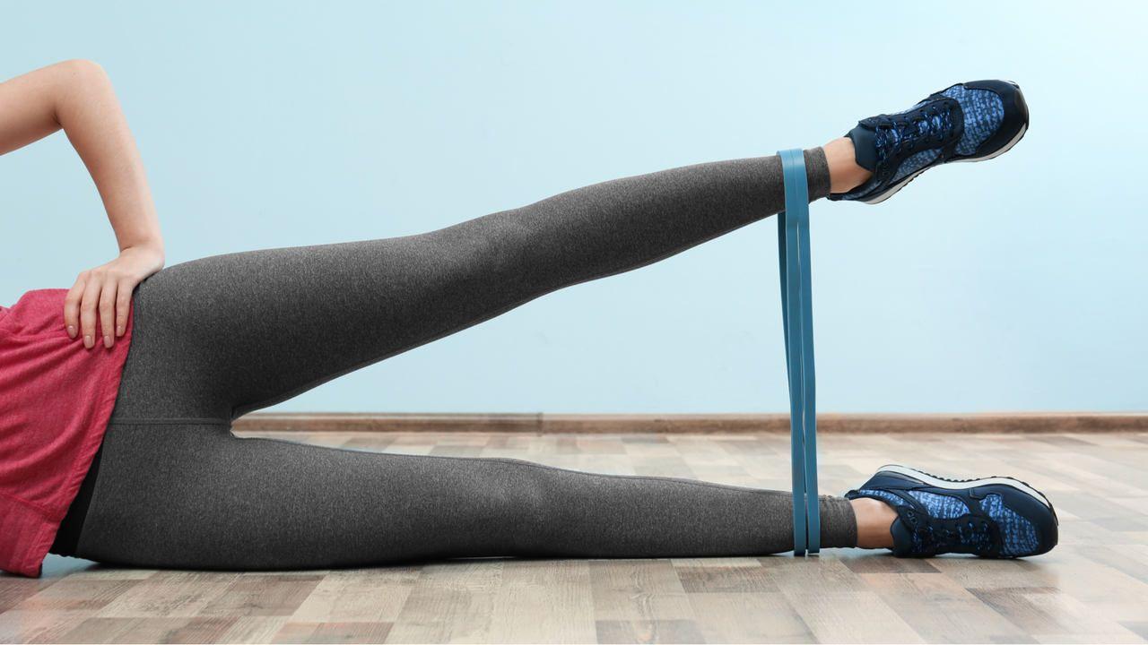 Mulher jovem deitada ao chão lateralmente, vestindo calça legging cinza, tênis preto e blusa vermelha, com mão na cintura e perna esquerda levantada em movimento de tesoura, utilizando elástico para treino azul na altura dos tornozelos
