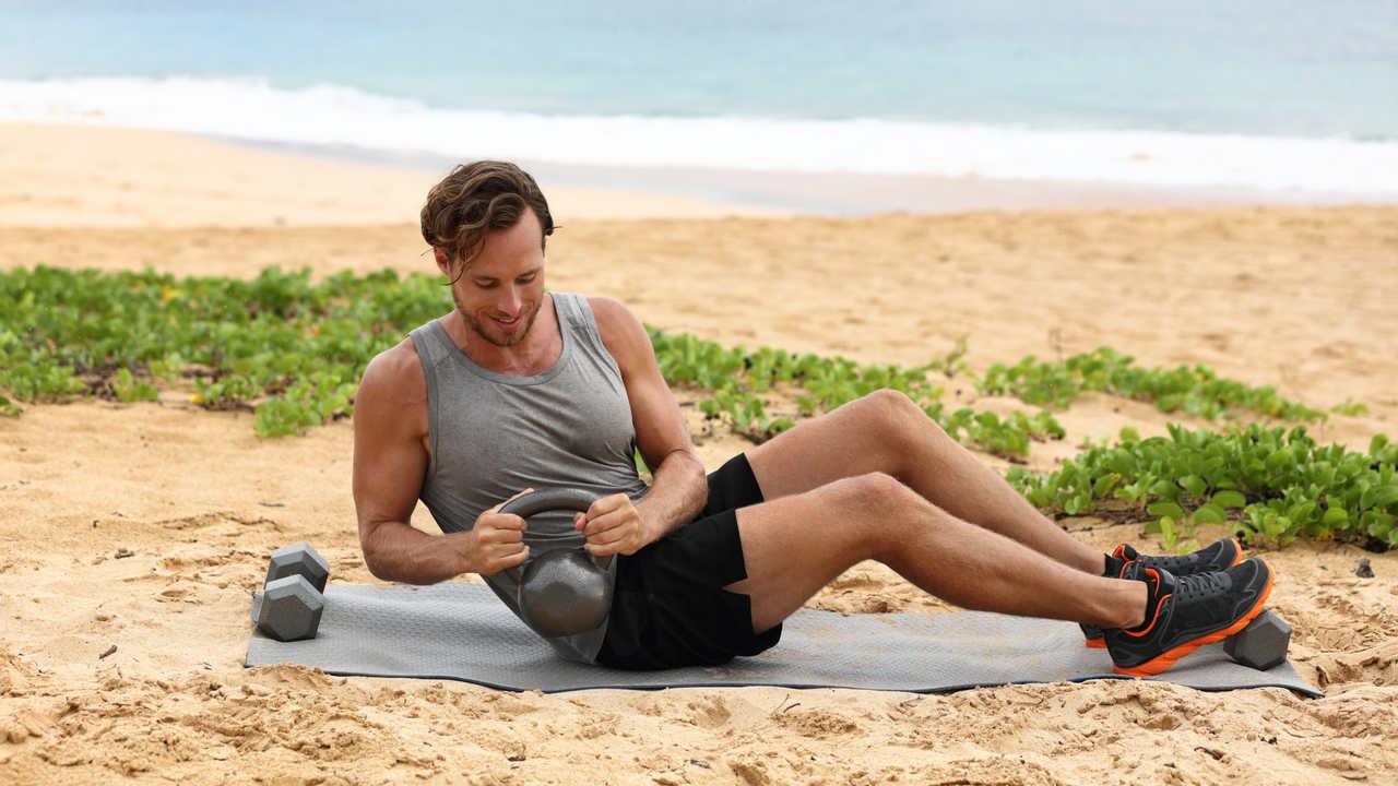Homem fazendo giro russo com kettlebell na praia