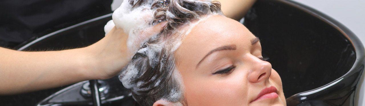 Mulher caucasiana lavando seu cabelo em ducha de alta pressão