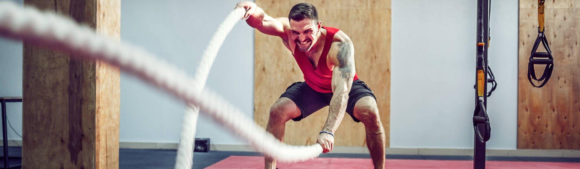 Homem caucasiano usando cordas para treinar