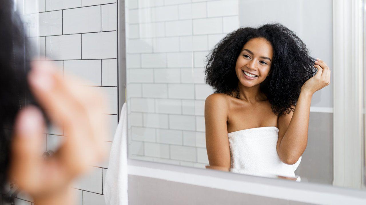 Mulher jovem em pé no banheiro segurando o cabelo cacheado
