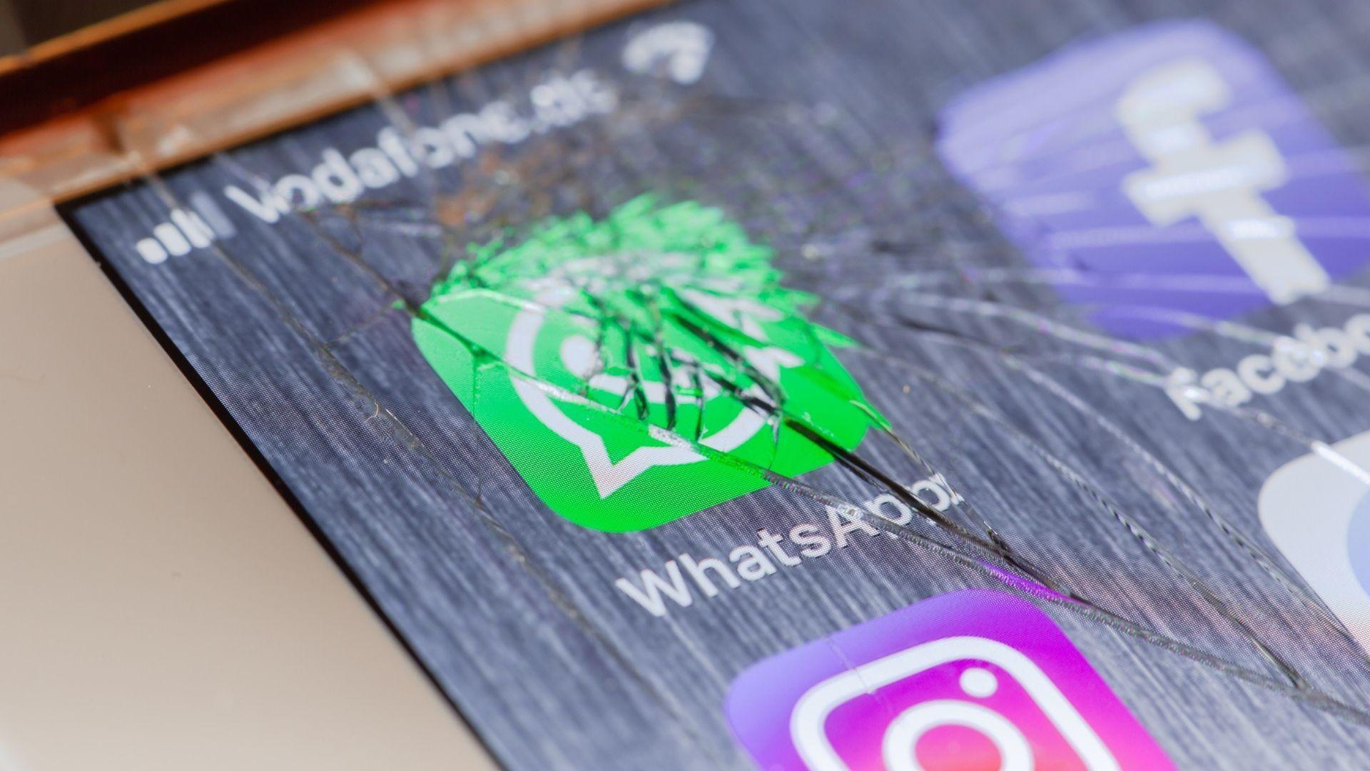 Tela de celular quebrada com ícone do WhatsApp