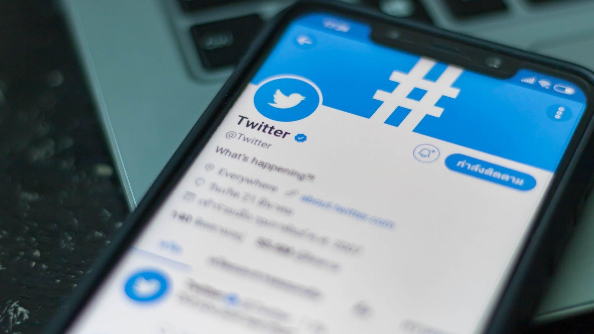 Celular aberto na página inicial da rede social Twitter em destaque